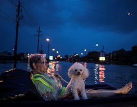 Aug. 27, 2017 – Houston, TX – A rescue helicopter hovers in the background as a woman and her poodle use an air mattress to float above floodwaters while waiting to be rescued from Scarsdale Boulevard. (Adrees Latif/Reuters)