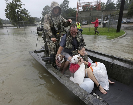 Aug. 28, 2017 – Spring, TX – John and Cathy Cservek hold their dogs Lacy and Iggy while being rescued from their home as floodwaters rise. (David J. Phillip/AP)