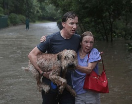Aug. 27, 2017 – Houston, TX – Andrew White (left) helps a neighbor down a street after rescuing her from her home in his boat. (Scott Olson/Getty Images)