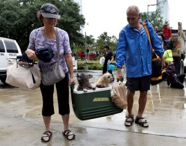 Aug. 27, 2017 – Houston, TX – A couple of evacuees carry their dogs into the the George R. Brown Convention Center. (Nick Oxford/Reuters)